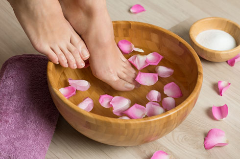 השרו את הרגליים במים פושרים ולא חמים כדי לכווץ את כלי הדם, ושדרגו עם כוס מלח נגד פטריות (צילום: Shutterstock)
