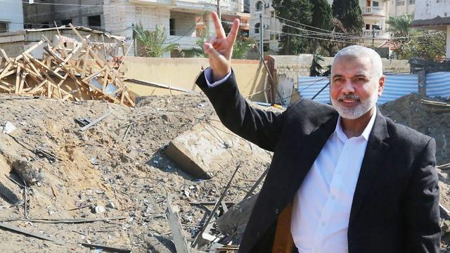 Ismail Haniyeh flashes a victory sign as he stands next to at the rubble of his office building in Gaza City, March 27, 2019