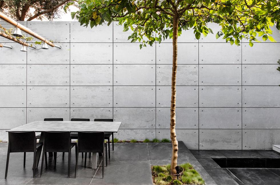 החצר מוקפת בקירות גבוהים שכוסו באריחי בטון גדולים, ורצפתה עשויה אבן ציפחה. היא מחולקת לאזורי משנה, פתוחה בחלקה לשמיים ובמרכזה עץ תות (צילום: איתי בנית)