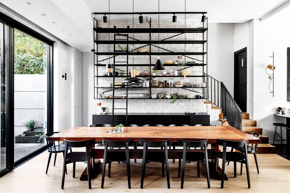 קומת הקרקע בבית בן ארבע הקומות משמשת את המשפחה ואת אורחי סדנאות הבישול וערבי האירוח. ספריית הברזל, הצמודה לקיר הלבנים, כוללת ארון אחסון תחתון, הכנות הגשה על המשטח מעליו, ותצוגה של כלים. שולחן האוכל, באורך 3.6 מטרים, נבנה בהזמנה מיוחדת מעץ אקליפטוס (צילום: איתי בנית)