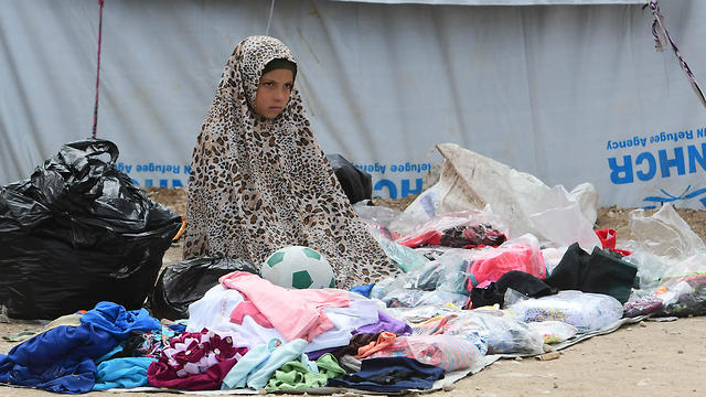 A Syrian girl sells second hand items in the Al-Hol camp for displaced people in northeastern Syria on March 28, 2019