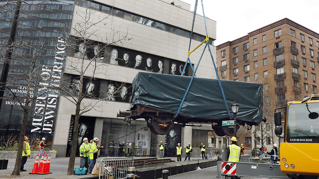 Cattle car used to transport Jews by the Nazis being lowered into place near the museum