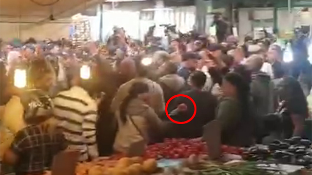 A young woman throwing a red vegetable at the prime minister in Hatikva Market (Screenshot)