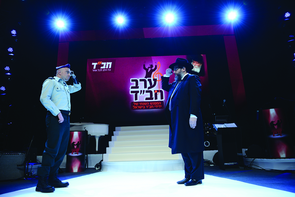 IDF Officer Ziv Shilon, who lost his arm in a terror attack, salutes with Chabad emissary in Israel Rabbi Yosef Aharonov Saluting each other (Photo: Mendy Hechtman)
