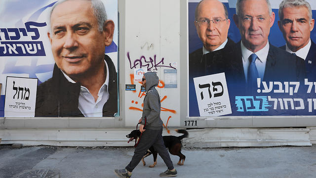 A man walks with his dog between election campaign billboards