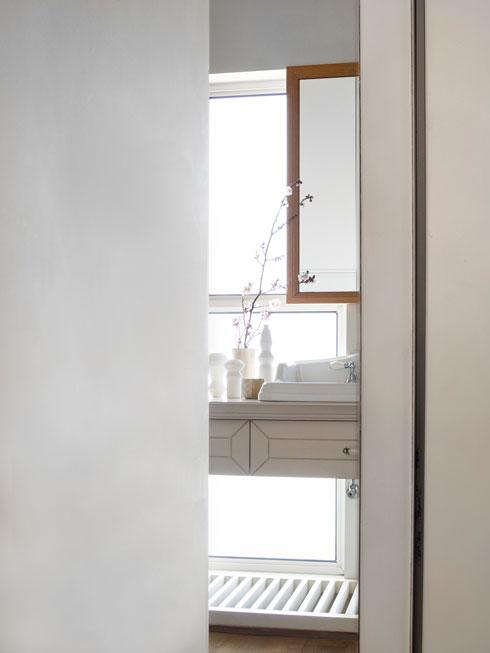 בחדר הרחצה סגנון רומנטי יותר, עם ארון כיור שדלתותיו עוטרו בידיו של נגר-אמן (צילום: נגה שחם פורת)