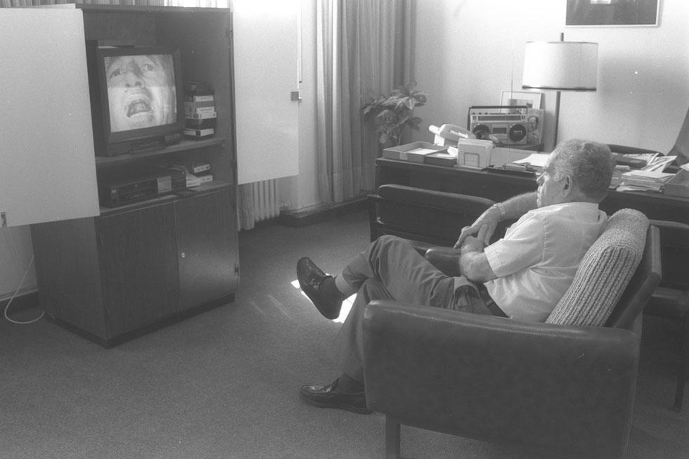 """1988: ראש הממשלה ומנהיג הליכוד יצחק שמיר צופה בתשדירי תעמולה לקראת הבחירות לכנסת ה-12 (על המסך: שמעון פרס) (צילום: מגי אילון, לע""""מ)"""
