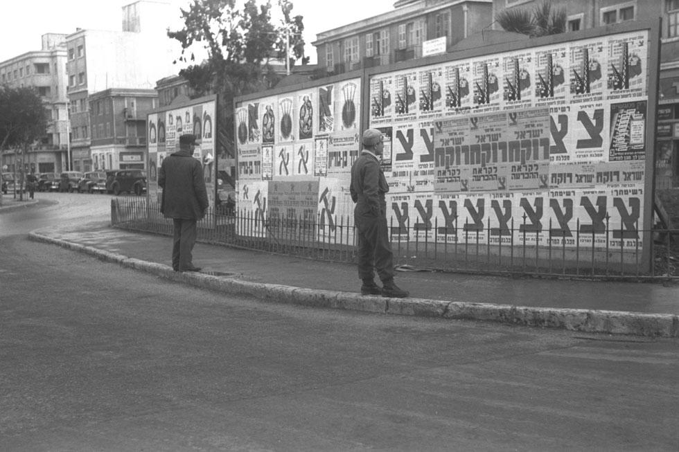 """1949: שניים מתושבי תל אביב סוקרים שלטי תעמולה לקראת הבחירות לאסיפה המכוננת (צילום: הוגו מנדלסון, לע""""מ)"""