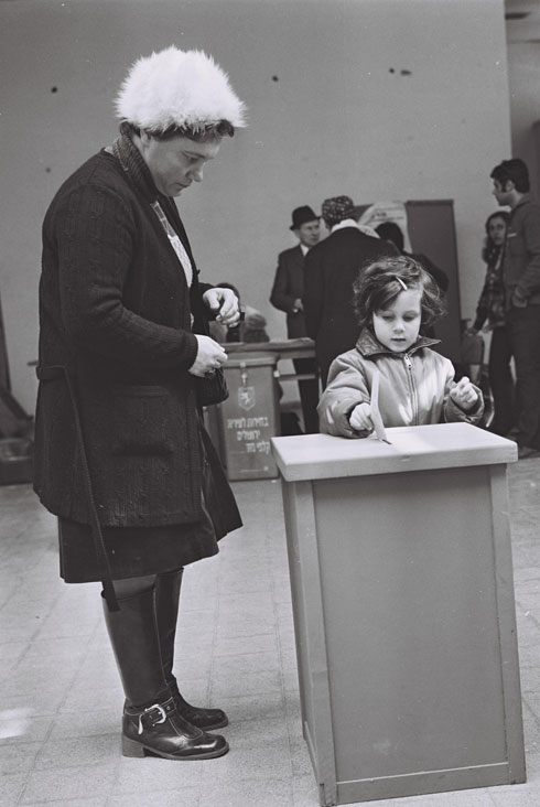"""1973: ילדה ירושלמית עוזרת לאמה להכניס את המעטפה לקלפי (צילום: יעקב סהר, לע""""מ)"""