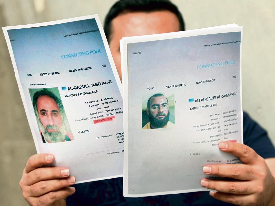 איש מודיעין עיראקי מציג את תמונותיהם של אבו בכר אל־בגדאדי (מימין) וסגנו עבד אל רחמן אל קאדולי, שחוסל על ידי האמריקאים ב־ 2016