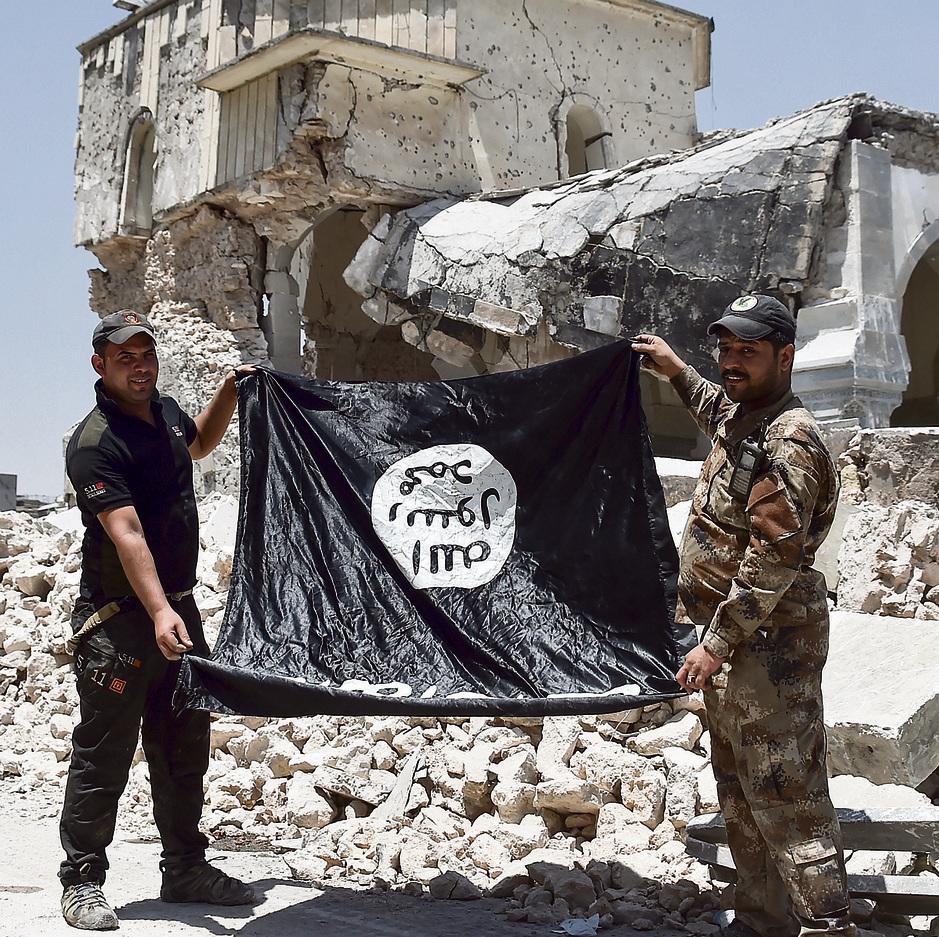 דצמבר 2018 . שני לוחמים בצבא עיראק מחזיקים את דגל דאעש הפוך, כשברקע מסגד א־נורי ההרוס, שבו הוכרז ארבע שנים קודם על הקמת ארגון דאעש