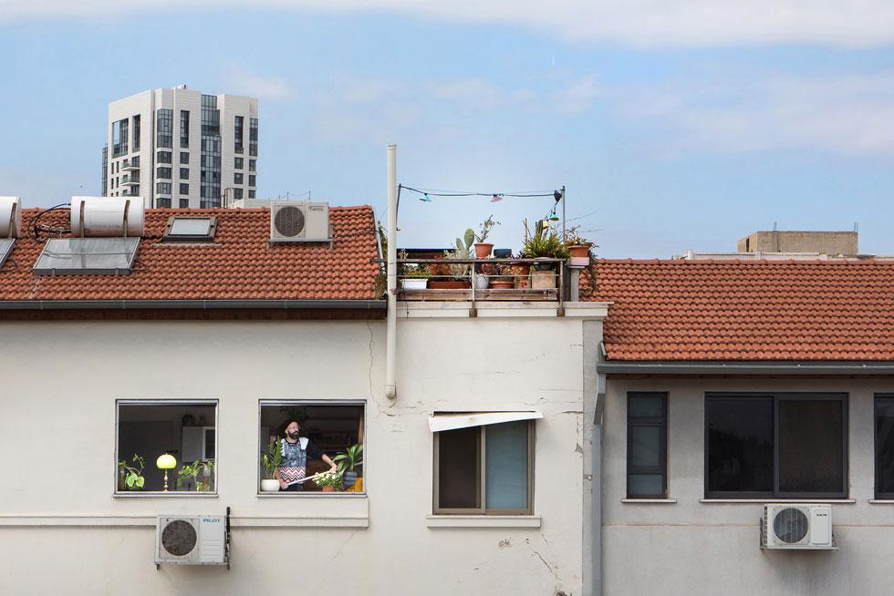 שי אליעזר צבי בחלון דירתו מעל שוק לוינסקי. ''בשעות היום נשמעות ברחוב צעקות סוחרים, ובלילה קולות בליינים'' (צילום: שירן כרמל)