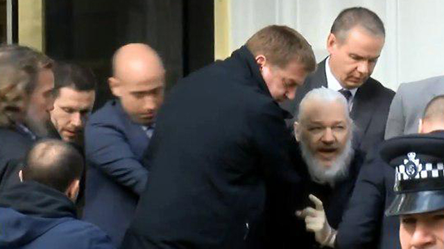 Assange being led out by police from the embassy
