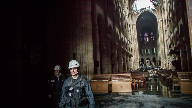 A man walks nside the damaged Notre Dame cathedral in Paris, Tuesday, April 16, 2019