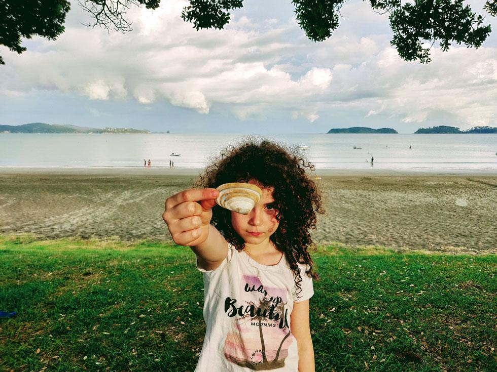 """תומר מוצאת צדף בחוף באוקלנד. """"היא צברה ביטחון ביכולת שלה להוביל ולמדה להיות עצמאית"""" (צילום: עידו צנג)"""