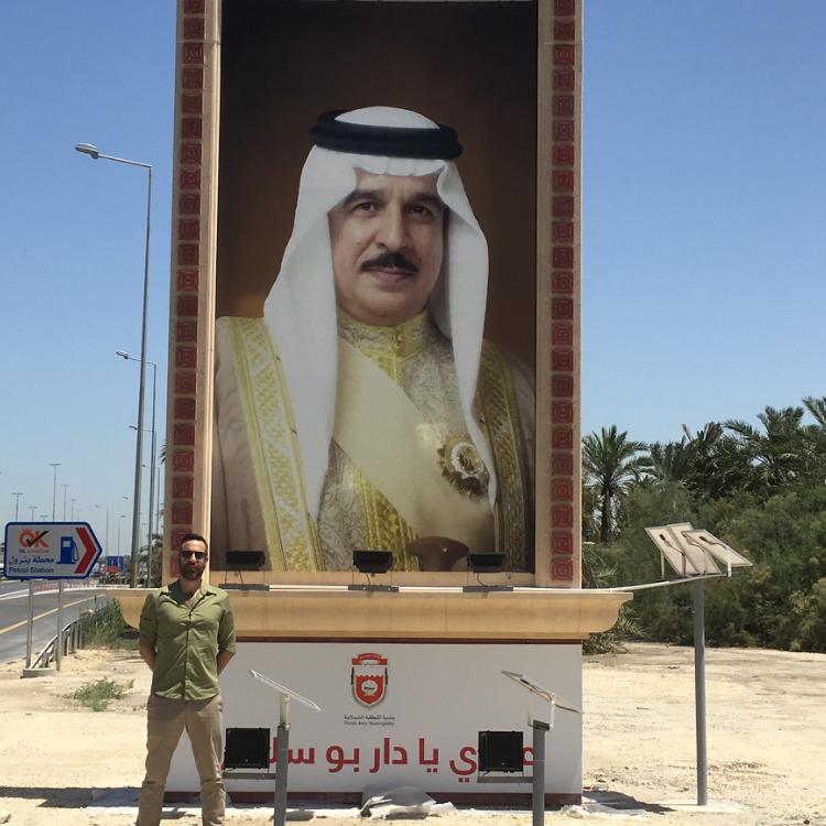 יניב חלילי על רקע תמונת המלך חאמד. אוחז בשרביט ענק של סמכויות