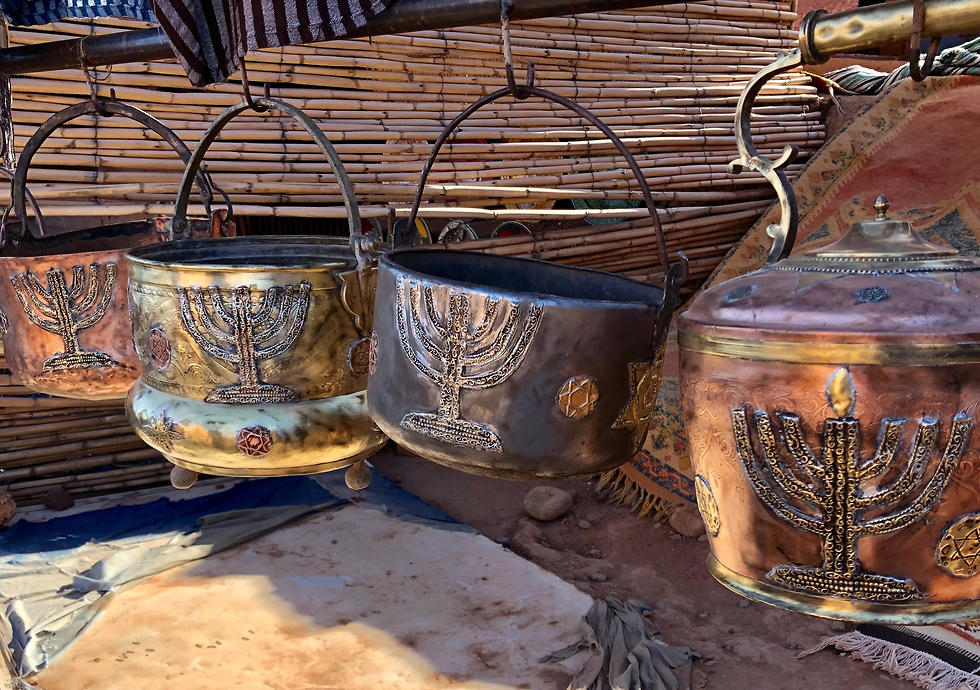 Cooking pots adorned with menorahs at an outdoor stall in Ksar of Ait-Ben-Haddou in southern Morocco