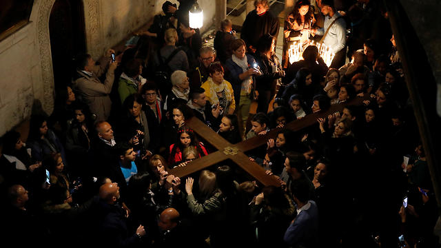 Worshippers carry a large wooden cross into the Church of the Holy Sepulchre on Good Friday (Photo: Reuters)