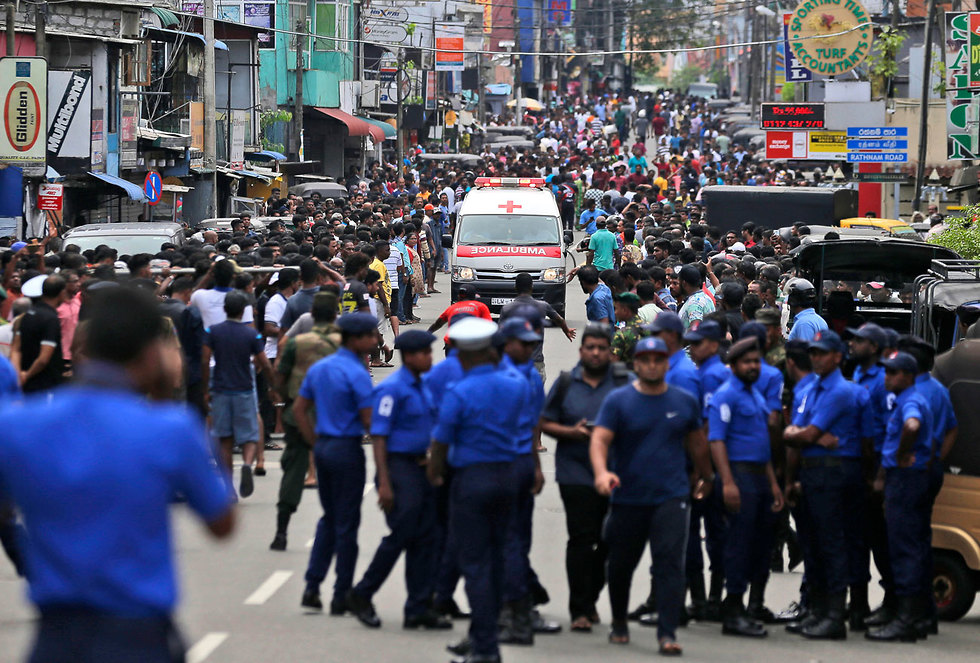 Police clear the street in Colombo after bomb blasts (Photo: AP)