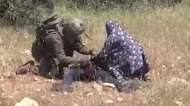 IDF medic treats the boy together with a local