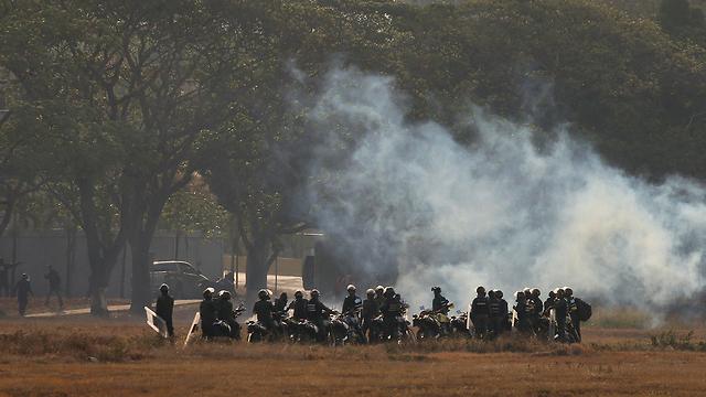 חיילים נאמנים ל נשיא ניקולס מדורו יורים גז מדמיע לעבר מפגינים תומכים חואן גוואידו ונצואלה ב קראקס (צילום: רויטרס)