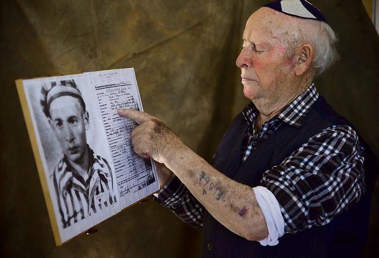 שטמברג אוחז בפסק הדין שקבע שהוא יהודי וקומוניסט, ושבעקבותיו נשלח לאושוויץ | צילום: אביגיל עוזי