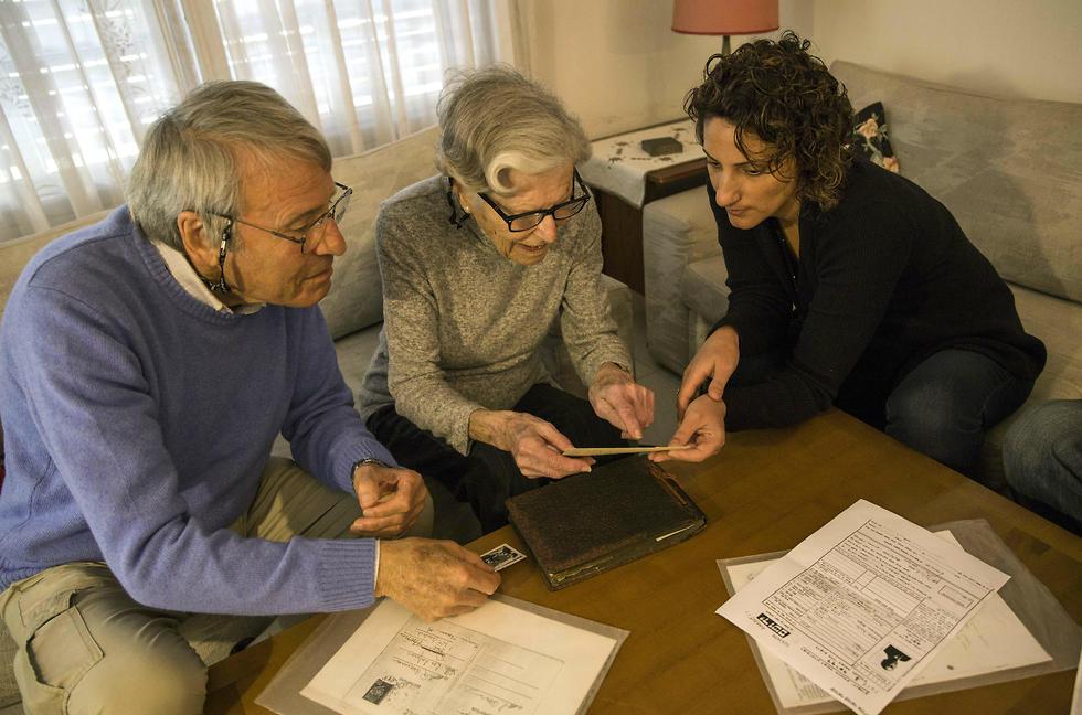 Holocaust survivors Rachel Zeiger 91, center, and her brother Moshe Akerman 84, left, speak with Orit Noiman, head of Yad Vashem's collection and registration center