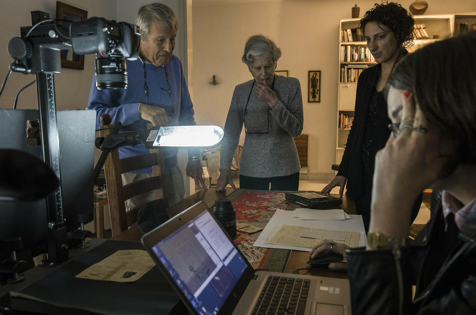 Zeiger, her brother Moshe Akerman and Orit Noima, head of Yad Vashem's collection and registration center, watch archivist Lena Shternberg reproduce holocaust era photographs and documents at their home
