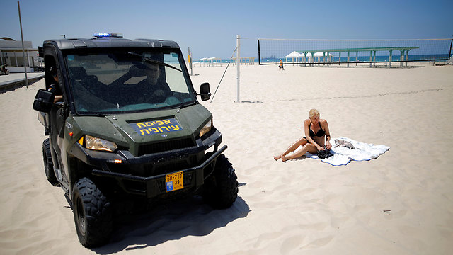רכב אכיפה עירונית ב אשקלון מבקש מרוחצים לעזוב את החוף (צילום: רויטרס)