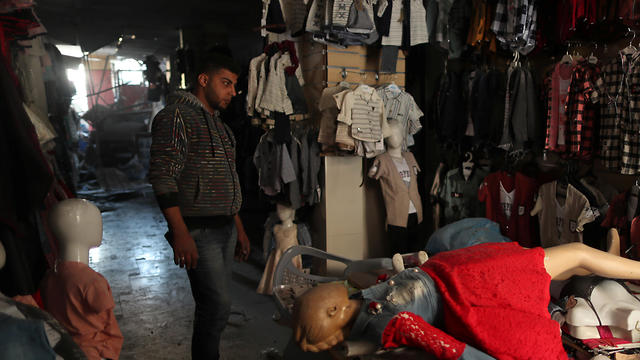 A Palestinian man checks his clothing store that was damaged in Israeli air strikes, in Gaza City, May 5, 2019