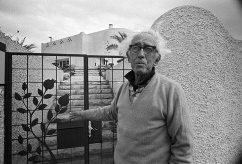 ראובן רובין לצד שער הכניסה, בו שולבו ארבעה רימונים, כמספר דיירי הבית (צילום: דוד רובינגר)