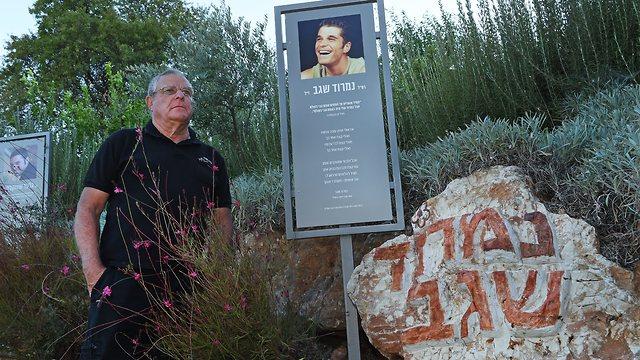 אדם עומד לצד אבן ועליה פנים של גבר (צילום: אפי שריר)