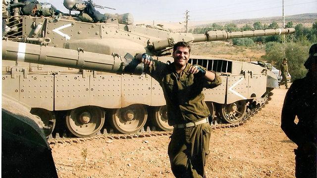חייל על מדים עומד ליד טנק (צילום: באדיבות המשפחה)