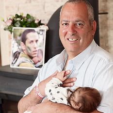 Avi and his baby daughter Ori, with a picture of Nadav in the background