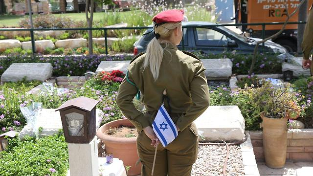 An IDF soldier visits Kiryat Shaul cemetery on the eve of Memorial Day (Photo: Moti Kimchi)