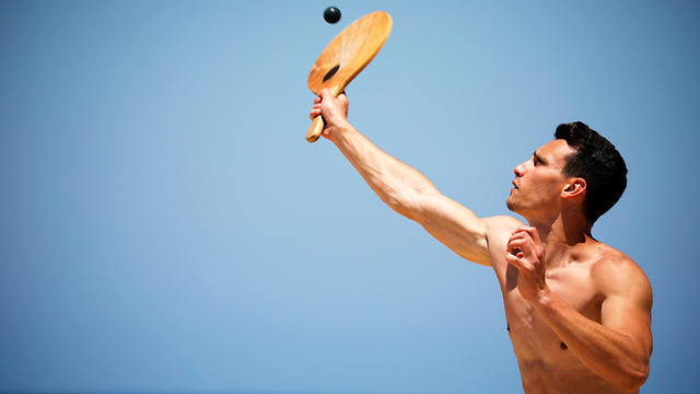 "A man plays paddle ball, known in Hebrew as ""matkot"", a popular Israeli sport, at a beach in Israel"
