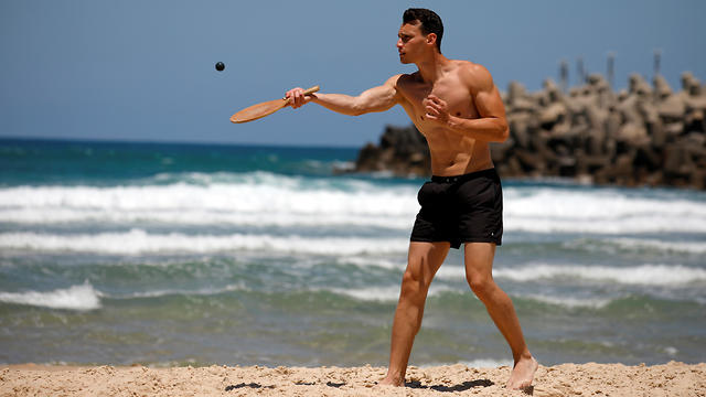 "A man plays paddle ball, known in Hebrew as ""matkot"""
