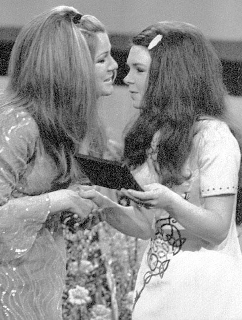 אירוויזיון 1970, אמסטרדם: קור (משמאל) מעניקה את הפרס לזוכה הבאה - דנה מאירלנד (צילום: AP)