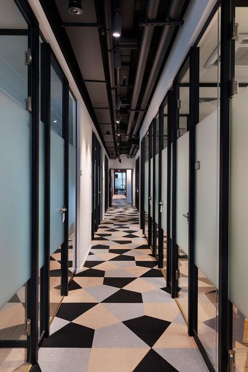 """אריחי שטיח בין שדרות המשרדים. """"לטשטש את התחושה המסדרונית""""  (צילום: אסף פינצ'וק)"""