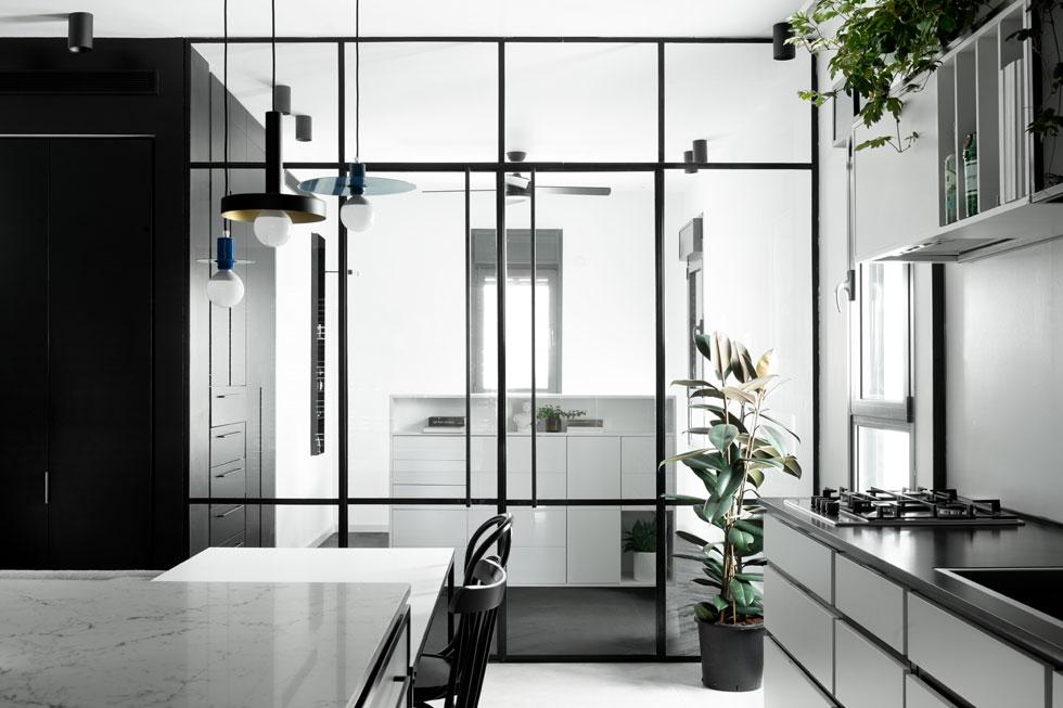קיר זכוכית בין המטבח לחדר השינה בדירה זוגית ביפו מאפשר אור משני כיוונים. שידת מגירות שתכנן המעצב איתן כהן מסתירה את המיטה מהעין (צילום: גדעון לוין)