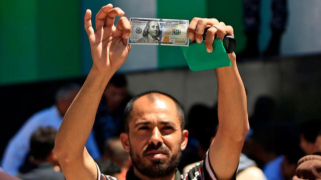 Gazan man receiving Qatari aid given destitute families (Photo: AFP) (Photo: AFP)