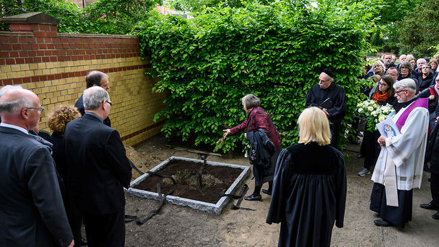 Saskia von Brockdorff throws soil on a box containing the remains of political prisoners executed by the Nazis   (Photo: AFP)