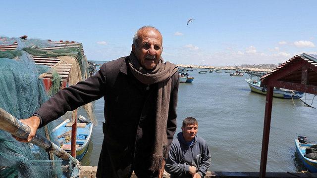 הדייג מחמוד אל-עאסי יושב על ספסל בטון בחוף בעזה ועליו הכיתוב