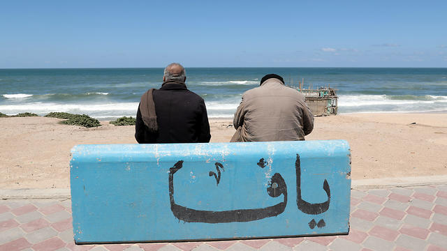 "Mahmoud Al-Assi, 73, who said that he was expelled with his family from Jafa, sits on a concrete bench adorned with a word reading ""Jaffa"", on a beach in Gaza City"