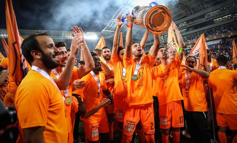 שחקני בני יהודה מניפים את גביע המדינה (צילום: עוז מועלם)
