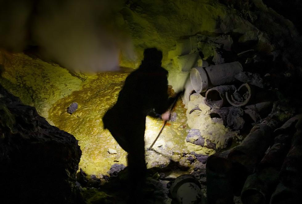 כורה שובר חתיכות גופרית במכתש איג'ן (צילום: ארז מרום)