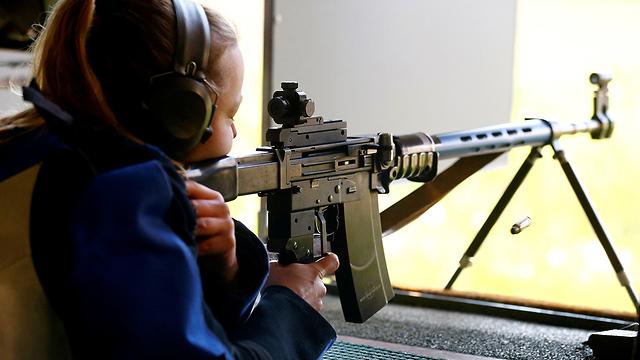 תמונת ארכיון של אישה יורה במטווח בשווייץ, שבה אימצו האזרחים במשאל עם הגבלות על כלי נשק (צילום: רויטרס)