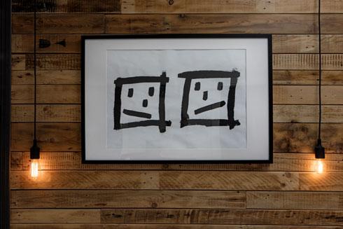 רישום שעופר שרבט ברגע בגואש שחור הפך ל''פורטרט זוגי'' (כפי שהוא מכנה אותו בחיוך) מעל המיטה (צילום: שירן כרמל)