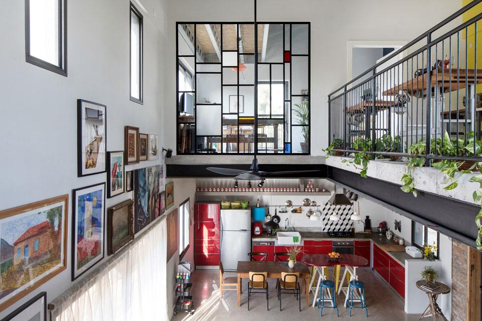 מבט מהמדרגות, בין שתי הקומות. למעלה חדר עבודה גדול של בני הזוג, שניהם עצמאים: היא הנדסאית אדריכלות ומעצבת פנים, הוא מפקח בנייה ומעצב גרפי. את הדלת אפשר לסגור, אבל קשר עין עם מרחבי הבית נשמר תמיד, בזכות קיר הזכוכית שהתקין עופר משאריות של ברזל וזכוכית (צילום: שירן כרמל)