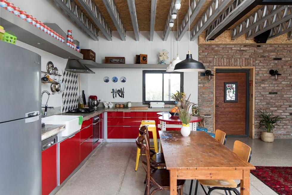 קיר הכניסה, שמקיף דלת מעץ גושני, עובה באמצעות לבנים אדומות הרצפה יצוקה מבטון, עם אגרגטים גדולים. במרכז המטבח שני שולחנות שונים: האחד דלפק אדום שצורתו אמורפית, מוקף בכיסאות בר צבעוניים, והשני שולחן עץ ישן (''מהסדנה של סבא''), לאכילה וליצירה  (צילום: שירן כרמל)